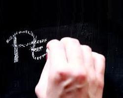 mano che scrive con il gesso sulla lavagna