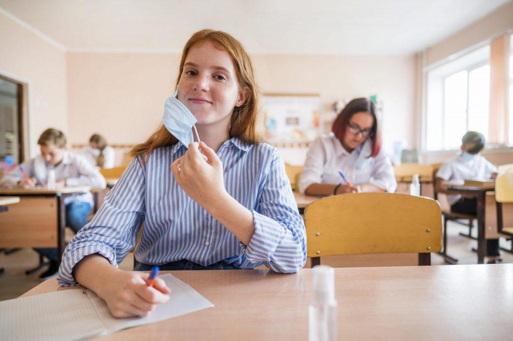 primo piano di uno studente con mascherina all'interno della classe