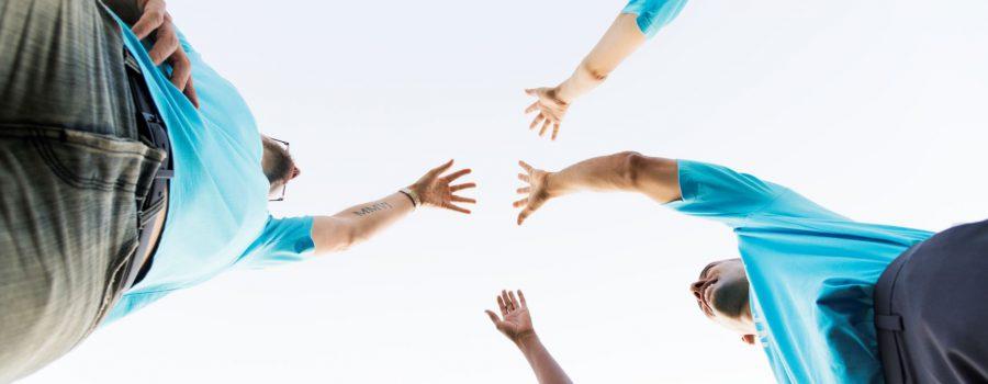 persone che si tendono la mano senza toccarsi